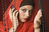 stock photo of burka  - Middle Eastern woman talking on cell phone - JPG