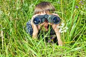 stock photo of binoculars  - Boy hiding in grass looking through binoculars outdoor - JPG