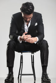 stock photo of stool  - Elegant young man in tuxedo looking down while sitting on a stool - JPG