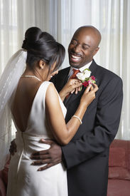 foto of lapel  - Bride pinning flowers onto groom - JPG