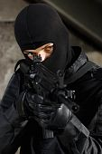 foto of extremist  - Man in black camouflage targeting with automatic rifle - JPG