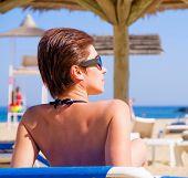 foto of sunbathing woman  - Woman sunbathing in bikini at tropical travel resort - JPG