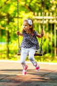 pic of seesaw  - Pretty little girl swinging on seesaw in summertime - JPG