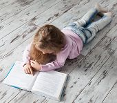stock photo of homework  - Child reading book at home - JPG