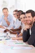 image of casual wear  - Group of business people in casual wear sitting in a row at the table and smiling at camera  - JPG