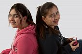 stock photo of teen pony tail  - Two identical Hispanic twin teen age sisters sitting back to back texting - JPG