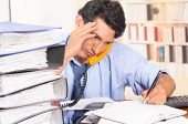 foto of overwhelming  - young stressed overwhelmed business man with piles of folders on his desk talking on the phone  - JPG