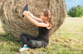 picture of haystack  - Young girl with device siting on the field close to haystack with hands up - JPG