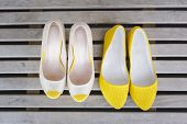 stock photo of ballet shoes  - yellow ballet shoes and high heels open toe shoes on wood boards - JPG