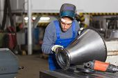 picture of inspection  - Welder inspecting a metal piece for quality control  - JPG