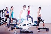 pic of step aerobics  - The word start now and fitness class performing step aerobics exercise against badge - JPG