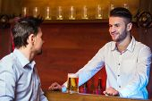 stock photo of bartender  - Cheerful young bartender is giving a mug with beer to the customer - JPG
