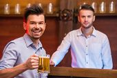 stock photo of bartender  - Cheerful young man in shirt with beer while sitting at the bar counter and bartender are looking at the camera - JPG