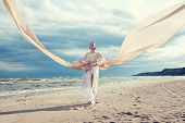 stock photo of long beach  - Fashionable portrait of beautiful model with very long dress like a wing - JPG