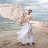 foto of long beach  - female model in long beige dress posing dynamic in the beach - JPG