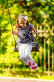 foto of seesaw  - Pretty little girl swinging on seesaw in summertime - JPG