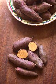 stock photo of ipomoea  - Overhead shot of raw purple sweet potato  - JPG