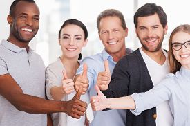 foto of stand up  - Group of cheerful business people in casual wear standing close to each other and showing their thumbs up - JPG