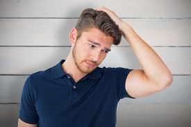 image of confusing  - Handsome young man looking confused against painted blue wooden planks - JPG