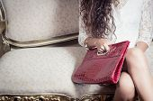 picture of bolivar  - legs and torso of model girl sitting on victorian sofa holding a red purse with right hand - JPG