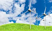 picture of grassland  - Eco power wind turbines generating electricity against partly cloudy blue sky background and grassland green earth concept - JPG