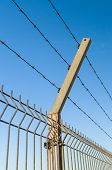 picture of barbed wire fence  - Security barbed wire fence against blue sky - JPG