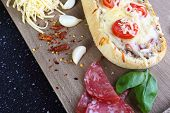 stock photo of baguette  - Home casserole on a baguette with cheese salami and tomato - JPG