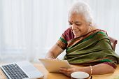 image of sari  - Mature Indian woman in sari using touchpad - JPG
