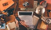 stock photo of messy  - Messy vintage desktop with laptop and male hands using a smart phone top view - JPG