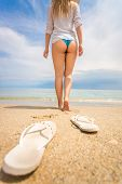 stock photo of off-shore  - Closeup shot of young woman taking off flip flops and and walking on the beach - JPG