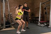 pic of squatting  - Young woman squatting with dumbbells in gym - JPG
