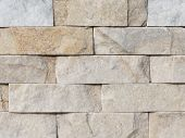 stock photo of cleaving  - wall of rough natural beige and gray marble stone with the cleaved surface laid horizontally like a brick - JPG