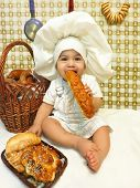 pic of bagel  - A sitting baby boy dressed as a baker with rolls and pastries, baby cook eats a bagel