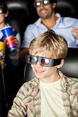 foto of watching movie  - Happy boy watching 3D movie with family in background at cinema theater - JPG