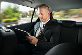 image of seatbelt  - Portrait Of A Businessman Using Digital Tablet While Travelling In A Car - JPG