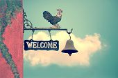image of blue-bell  - Classic Door Bell with silhouette of chicken vintage welcome label on blue sky with cloud - JPG