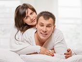 stock photo of laying-in-bed  - Happy smiling couple laying laughing in bed with light window background - JPG