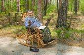 foto of coniferous forest  - Senior man is having rest in coniferous forest sitting on a wicker rocking - JPG