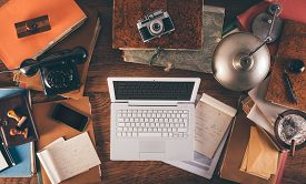 picture of messy  - Messy vintage desktop with laptop phone lamp camera and folders top view - JPG