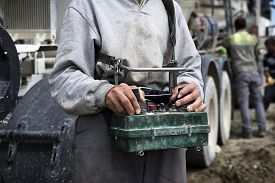stock photo of boom-truck  - Concrete pump operator with remote control for boom pump truck at construction site - JPG