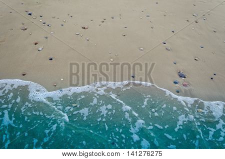 poster of Wave of the sea on the sand beach. Sand and wave background. Soft wave of blue ocean on sandy beach. Sea wave over sand. Background of wave on the sand.