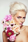 Portrait of young beautiful platinum blonde girl with stylish make-up, prom hairdo and flowers poster
