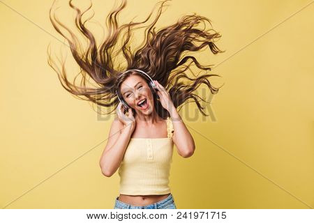 poster of Image of amusing woman 20s singing and having fun with shaking hair while listening to music via hea