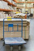 Shop Of Building Materials. Racks With Boards, Wood And Building Materials. Packed Boards In The Bui poster