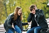 conflict in young people relationship. Furious anger girl and man stopped ears with hands