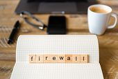 Closeup On Notebook Over Wood Table Background, Focus On Wooden Blocks With Letters Making Firewall  poster