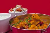 image of raita  - Chicken and chickpea curry in a balti bowl served with mint raita and onion salad - JPG