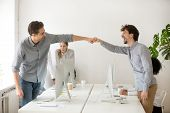 Cheerful Male Colleagues Fist Bumping Celebrating Successful Teamwork In Office, Friendly Happy Moti poster