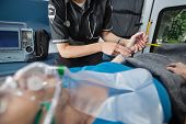 stock photo of triage  - Detail of EMT worker measuring pulse on arm of senior woman patient - JPG