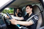 stock photo of dispatch  - Female EMT calling dispatcher on radio  - JPG